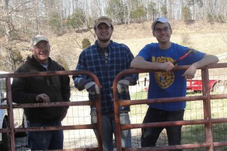 Tim Sims, left, a parishioner at Holy Cross Church in Burkesville, Ky., stood at a newely-erected farm gate with two students from the College of Holy Cross in Worchester, Mass., who'd helped erect it.