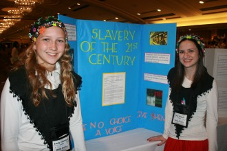 Emily Kapple and Emily Thomson, freshman at Holy Cross High School, stood in front of the display for Croatia at the March KUNA conference. Holy Cross also presented the World Service Organization with a check for $205 and turned in 255 Shoes to the Edge Out Reach Program.