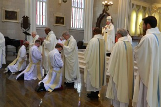 Priests laid their hands on, from left, Father Christopher Rhodes, Father Stuart Priddy and Father David Carr during their ordination to the priesthood May 26 at the Cathedral of the Assumption.