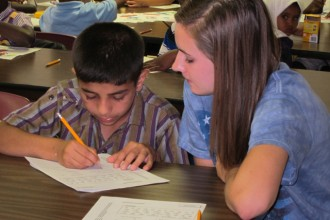 Erin Walsh of Sacred Heart Academy, right, helped Shahram Safiullah from Tajikistan with his work at Catholic Charities' English language school recently. The agency is hoping to get more people involved in its work with refugees. (Photo Special to The Record)