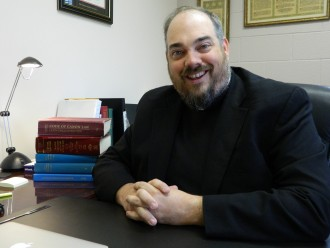 Father Paul Beach, pastor of St. Martin of Tours Church and a judge in the archdiocese's Metropolitan Tribunal, discussed the nature of annulments and marriage at his office July 26. His copy of the Code of Canon Law sat next to him atop a stack of other books. (Record Photo by Marnie McAllister)