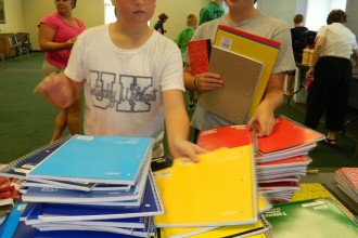 Holy Spirit School students Kate Gaeta, left, and Erin Herbert sorted donated school supplies along with more than a dozen other young people July 31. Holy Spirit Church collected the supplies last month for Catholic school students who are assisted by the Community Catholic Center. The center provides scholarships, transportation and other services for children in West Louisville who want to attend Catholic schools. (Record Photo by Marnie McAllister)