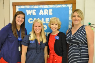 Katie Wetterer, Laura Carby, Dr. Beverly McAuliffe and Andrea Gordon Ruley stand together in the hallway of Holy Family School. Wetterer, Carby and Ruley, former students of McAuliffe, now work with the new principal at Holy Family.