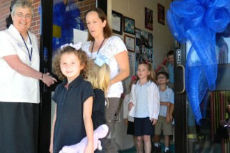 Sister Michael Marie Friedman, principal of St. James School in Elizabethtown, held a door for students at the school on Monday. A blue ribbon marking the school's designation as a Blue Ribbon School of Excellence decorated the school doors.