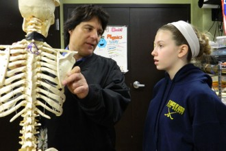 """St. Francis of Assisi teacher Fred Whittaker pointed out the hyoid bone on """"Skinny Bill"""" the skeleton to seventh-grader Amelia Ansert during a recent science class. Whittaker will receive the Father Joseph McGee Award for Outstanding Catholic Educator on March 20 at the Salute to Catholic School Alumni. (Record Photo by Marnie McAllister)"""