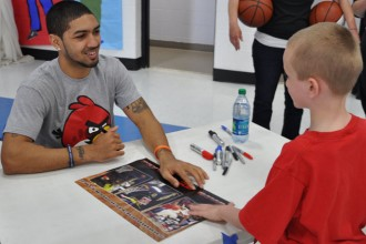 Peyton Siva, a member of the 2013 National Championship U of L men's basketball team, signed an autograph for a student at St. Gabriel School Thursday, April 18. Siva visited the school to speak to students about perseverance, hard work and the importance of education. (Record Photo by Jessica Able)