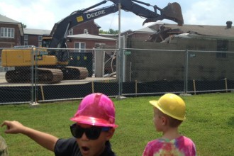 Youngsters at St. Joseph Children's Home excitedly watch as a huge piece of machinery begins destruction of buildings to make room for new residential cottages at the Frankfort Avenue facility. The annual St. Joseph Children's Home Picnic will be held this year on Aug. 10. (Photo Special to The Record)
