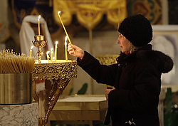 Marta Borodayko lights a candle following a prayer service to pray for people in Ukraine Feb. 25 at St. Nicholas Ukrainian Catholic Cathedral in Chicago. (CNS photo/Karen Callaway, Catholic New World)