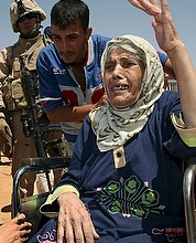 An elderly Iraqi woman fleeing violence gestures at the Al Waleed refugee camp in Iraq Aug. 19. One group of sick, elderly Iraqi Christians said they defied terrorist demands to convert to Islam or be killed.(CNS photo/Morris Bernard, UNHCR handout via EPA)