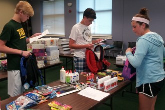 Holy Spirit Church parishioners, from left, Andrew Lechleiter, a freshman at St. Xavier High School, Patrick Donovan, a junior at St. Xavier and Kate Gaeta, a seventh-grader at Western Middle School for the Arts helped sort donations for Community Catholic Center recently.