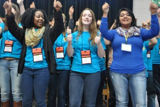 "Members of the Archdiocese of Louisville's Youth Advisory Board perform hand motions to the song ""I'm Trading My Sorrows"" at the Nov. 22 Quest youth rally held at Bellarmine University's Frazier Hall. (Record Photo by Jessica Able)"