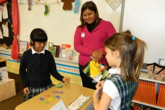 Second-graders Brandy Paisano, left, and Emily Roussel, right, took part in a lesson about bartering at St. Rita School last week. Brandy's mom, Blanca Salinas, looked on. Brandy is one of about two dozen Latino children now attending the school, thanks to an initiative to increase their enrollment. (Record Photo by Marnie McAllister)