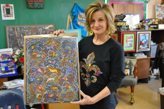 Ann Smith, an art teacher at Ascension School, displays art work created by her students that's being sold by Dee's Crafts to help fund art programs in three local schools. (Record Photo by Jessica Able)
