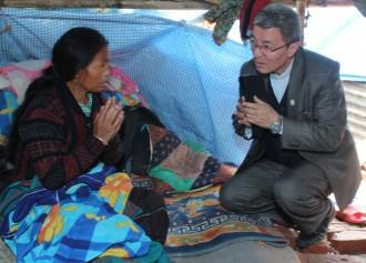 Bishop Paul Simick of Nepal visits an injured Catholic earthquake survivor April 30 in remote Banyatar parish perched on a hilltop overlooking Kathmandu. (CNS photo/Anto Akkara)