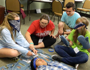 Teenagers, from left to right, Kimberly Malone, Kacie Gaekle, Jack Wolfram and Tessa Grissom and Jason Patrana, foreground, worked together to assemble a puzzle during a team-building activity at the annual Christian Leadership Institute held July 6 to 10 at the Flaget Center. (2015 Record File Photo)