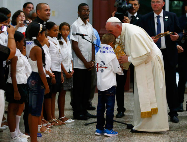 Pope Francis receives a gift from children at the shrine devoted to Our Lady of Charity in El Cobre, Cuba, Sept. 21, 2015. (CNS photo/Tony Gentile, Reuters)
