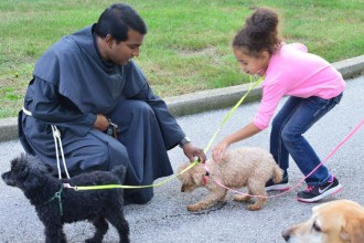 Conventual Franciscan Friar Tony Vattaparambil, sacramental moderator of Holy Family Church, petted a dog at a blessing of animals prayer service at the parish, 3926 Poplar Level Road, on Oct. 4, the feast day of St. Francis of Assisi. (Photo Special to The Record)