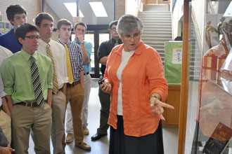 Linda Schork pointed out the relic of St. Junipero Serra to a group of students Sept. 24 in the St. Xavier High School media center.