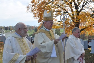 Deacon Robert Markert, left; Archbishop Joseph E. Kurtz, center; and Father Pepper Elliott, right, prepare to begin Mass at the All Souls' Day liturgy Nov. 2 at Calvary Cemetery, 1600 Newburg Road.
