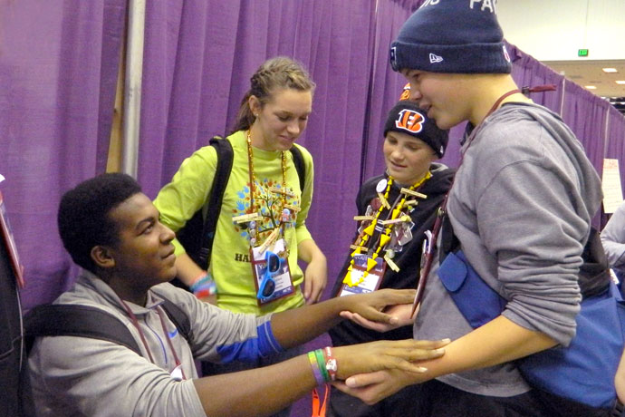 During a break at the National Catholic Youth Conference in Indianapolis Nov. 21, Shaquan Hays, seated, and Nicholas Terrell played a game while Kirsten Crepps, center, and Will Taylor looked on.  The four teens were part of the delegation from the Archdiocese of Louisville. Record Photo by Ruby Thomas