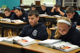 Brandon Ballard, left, and Kailee Miller, both eighth-graders at St. Catherine Academy in New Haven, Ky., read from their books during class on Nov. 5. The school in Nelson County has seen a 15 percent increase in student enrollment during the course of the last year. (Record Photos by Jessica Able)