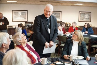 Archbishop Joseph E. Kurtz spoke to Robert Hart, Paula Fangman and Diva Justice, from left, at the Catholics @ the Capitol event Feb. 9 at the Capital Plaza Hotel.