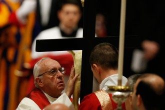 Pope Francis reverences the crucifix during the Good Friday service in St. Peter's Basilica at the Vatican March 25. (CNS photo/Paul Haring)