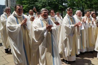 Priests of the Archdiocese of Louisville, and several who were visiting, applauded newly ordained priests after Mass at the Cathedral of the Assumption May 28. Fathers Sean McKinley and Wilfredo Fernandez were ordained by Archbishop Joseph E. Kurtz that morning. (Record Photo by Marnie McAllister)
