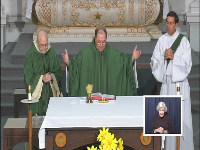 A still image shows Deacon Robert Markert, Father Nicholas Rice and Deacon Mark Rougeux, from left, during a recent filming of Mass of the Air. Norma Lewis can be seen in the inset box interpreting for hearing impaired viewers. Father Rice, who founded the broadcast ministry in 1977, is retiring as director. Deacon Rougeux, who ministers at St. Patrick Church, will be the new Mass of the Air director effective July 1. (Photo Special to The Record)