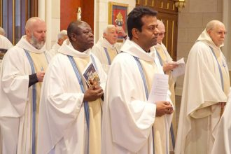 The procession into the Cathedral of the Assumption during the Chrism Mass earlier this year included, from left, Father William Bowling of St. Augustine Church in Lebanon, Ky.; Father Emil Kander from the Diocese of Jasikan in Ghana and Carmelite of Mary Immaculate Father George S. Illikkal from India. Currently 18 priests from other countries are serving in the Archdiocese of Louisville. (Record File Photo by Marnie McAllister)