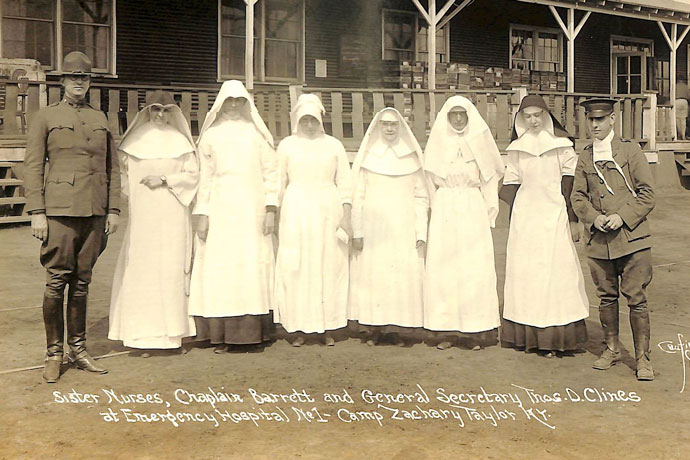 Women religious representing orders that nursed soldiers at Camp Taylor during the flu epidemic in 1918 are pictured outside a camp hospital along with a chaplain who recruited them, Father Regis Barrett, left, and General Secretary Thomas Clines. The sisters represented, from left, the Dominican Sisters, Sisters of Loretto, Sisters of Charity of Nazareth, Sisters of Mercy, Franciscan and Ursuline sisters. (Photo Special to The Record)