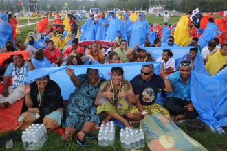 Pilgrims from the Wallis and Futuna Islands in the South Pacific take shelter during a storm at the opening Mass for World Youth Day July 26 at Blonia Park in Krakow, Poland. (CNS photo/Bob Roller)