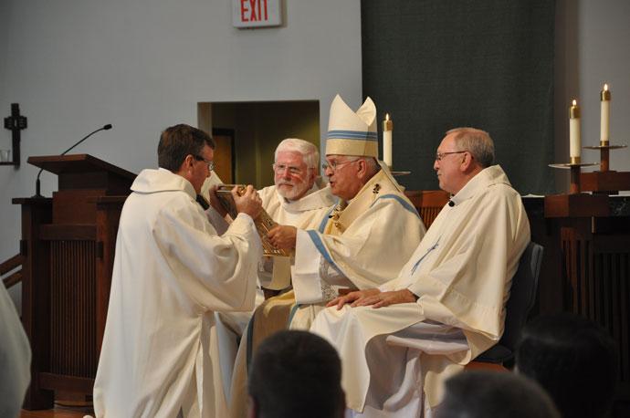 Archbishop Joseph E. Kurtz presented the Book of Gospels to Deacon Bruce J. Warren during the Aug. 20 diaconate ordination.