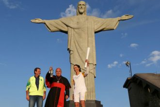 Cardinal Orani Tempesta of Rio de Janeiro holds the Olympic flame Aug. 5 as Rio Mayor Eduardo Paes and former Brazilian volleyball player Isabel Barroso look on in front of the Christ the Redeemer statue. (CNS photo/Pilar Olivares, Reuters)