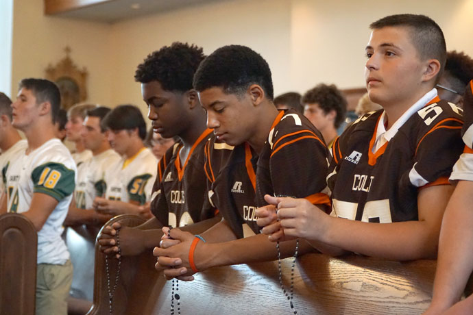 DeSales High School freshmen, from left, Quentin Mitchell, Anthony Barlow and Caleb Mattingly prayed the rosary at a service sponsored by SportsLeader July 27 at Holy Family Church on Poplar Level Road. They were among about 600 football players who attended the event where they also heard from Fathers Michael Wimsatt and Shayne Duvall of the Vocation Office. (Record Photo by Ruby Thomas)