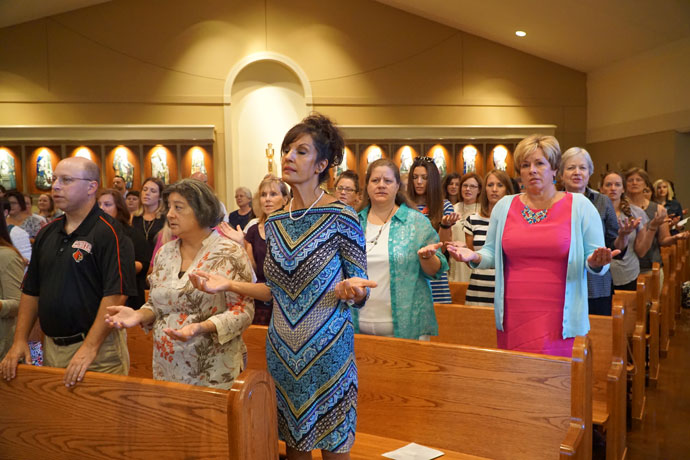"""Teachers pray the """"Our Father"""" at the annual liturgy held prior to the start of the school year, held this year at St. Lawrence Church."""