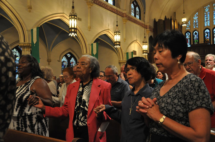 People attending a prayer service for peace Sept. 9 at St. Martin de Porres Church joined hands and prayed the Lord's Prayer. The service drew a diverse group of about 600 people. (Record Photos by Jessica Able)