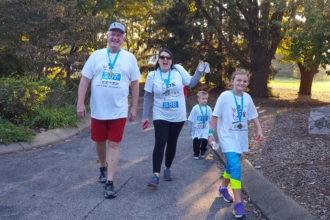 Archbishop Joseph E. Kurtz walked with a family after they finished the race. The archbishop placed second in his age group.