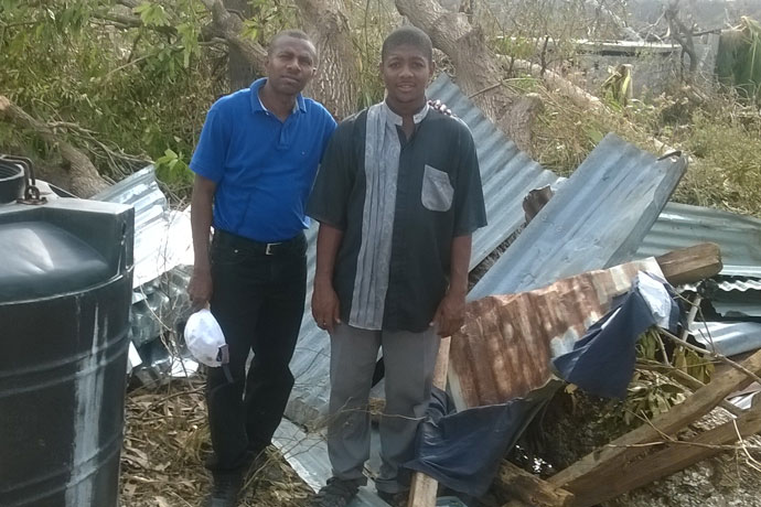Father Jean Bernadin Paul, pastor of St. Louis De Gonzague Church in Bonbon, Haiti, right, and Bernard Cadet, stand in front of wreckage in Bonbon caused by Hurricane Matthew. St. Bernadette Church in Prospect, Ky., and the Haiti parish have a twinning relationship. (Photo Special to The Record)