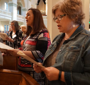 "Women from St. Patrick Church in Louisville, above foreground from left, Jonna O'Bryan and carrie Williamson, sang during the closing liturgy of the ""Women of the Church"" conference Oct. 8."
