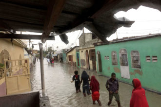 People wade through a flooded street Oct. 4 in Port-au-Prince, Haiti, as Hurricane Matthew sweeps through the island nation. The city of Les Cayes and coastal towns and villages in southwestern Haiti were experiencing the most destruction as the storm made landfall at dawn with 145-mile-an-hour winds. (CNS photo/Carlos Garcia Rawlins, Reuters)