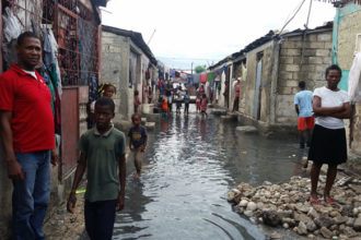 Residents stand outside their homes Oct. 5 in Cite Soleil, a slum in Port-au-Prince, Haiti, after Hurricane Matthew swept through the island nation. Rescue workers in Haiti are struggling to reach parts of the country cut off by Hurricane Matthew, the most powerful Caribbean storm in nearly a decade. (CNS photo/courtesy Malteser International)