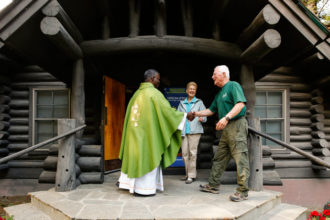 Father Lucas Kazimiro Simango greets Massgoers as they enter the log Chapel of the Sacred Heart in Grand Teton National Park in Wyoming Aug. 7. (CNS photo/Nancy Wiechec)