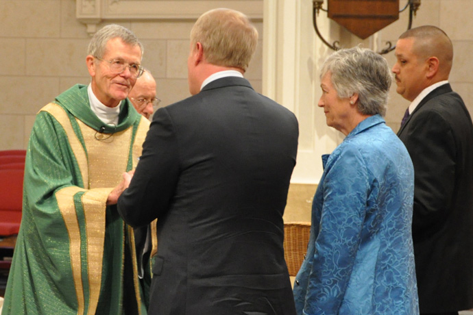 Father William Fichteman received the bread and wine during the offertory at a 2014 Mass at the Cathedral of the Assumption celebrating the 150th anniversary of St. Xavier High School. (Record File Photo by Jessica Able)