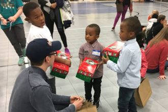 "The joy  of giving  About 100 children served by the Society of St. Vincent de Paul's Family Success Center packed shoeboxes with donations for children around the world through ""Operation Christmas Child"" on Dec. 1. The children wanted to help people in need after hearing from local teens, Olivia and Gabe Feinn, about their efforts to help children in the Congo. About 100 teenage volunteers helped the children pack the donations. The Feinn children funded the project by selling their homemade cakes.  Photo Special to The Record"