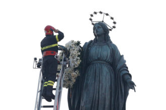A firefighter salutes after placing a wreath on a statue of Mary overlooking the Spanish Steps in Rome Dec. 8, the feast of the Immaculate Conception. Rome's firefighters have observed the tradition every year since 1857. (CNS photo/Paul Haring)