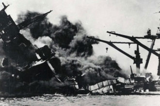 "A ship is seen sinking during the Japanese attack on Pearl Harbor Dec. 7, 1941. A Catholic military chaplain and historian says the attack on Pearl Harbor, even 75 years later, continues to rivet the attention of Americans because it was ""such a powerful event."" (CNS photo/Pearl Harbor Museum)"
