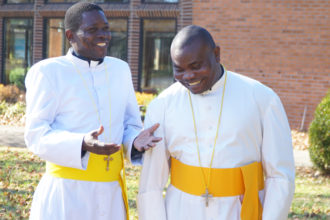 Father George Otuma, left, who serves at Holy Spirit Church, and Father Deogratias Ssamba, who serves at St. Peter the Apostle Church, were photographed on the campus of St. Andrew Academy Dec. 1. The Uganda natives are the newest foreign-born priests to arrive in the Archdiocese of Louisville. (Record photo by Ruby Thomas)