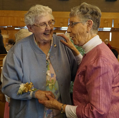 Ursuline Sister of Mount Saint Joseph Grace Simpson, left, greeted Sister of Charity of Nazareth Joan Wilson at the World Day of Consecrated Life Mass Feb. 5 held at St. Stephen Martyr Church. Sister Simpson celebrated 60 years of religious life at the liturgy.