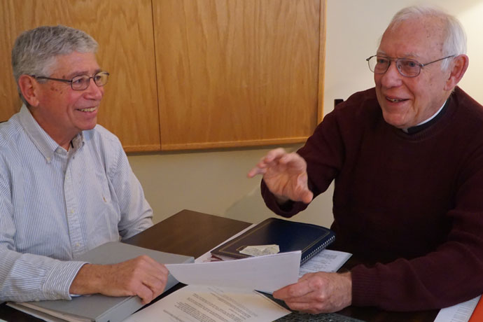 Mike Kolb, left, and Father Joseph Graffis talked about their experience at the World Meeting of Popular Movements during an interview in Father Graffis' office Feb. 20. The meeting took place Feb. 16-19 in Modesto, Calif. (Record Photo by Ruby Thomas)